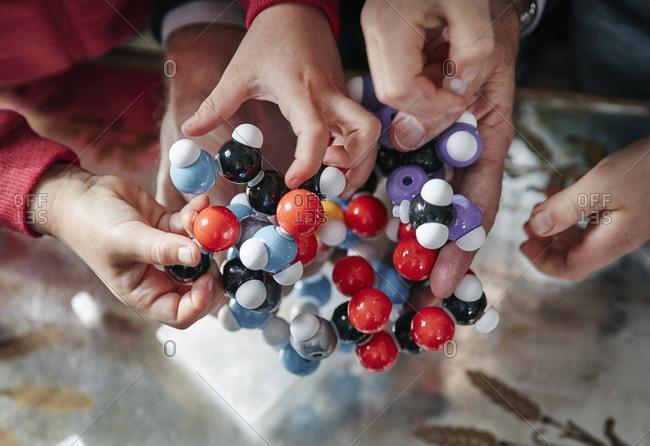 Hands of grandfather and grandchildren assembling molecular model