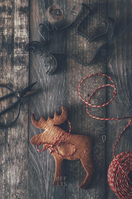 Elk-shaped cookie- cookie cutter- scissors and string on dark wood