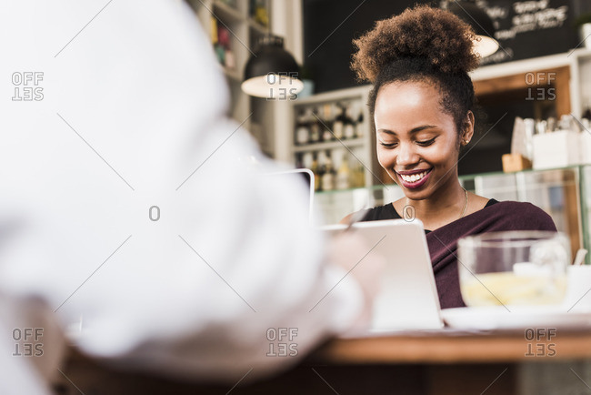 Smiling waitress at counter in a cafe with customer