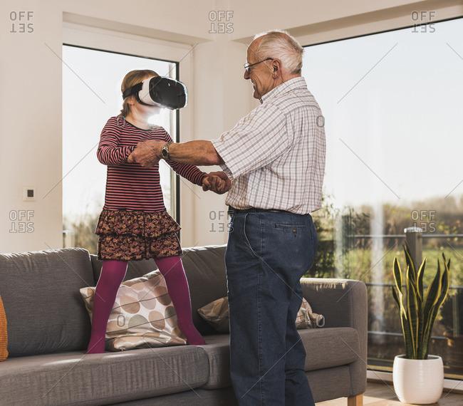 Grandfather holding granddaughter- using VR glasses