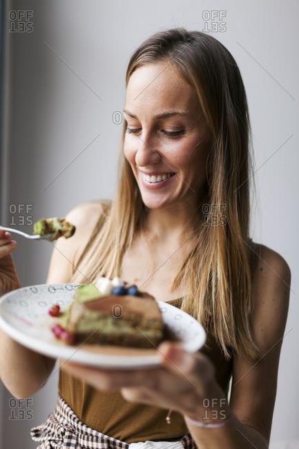 Woman eating vegan matcha cake