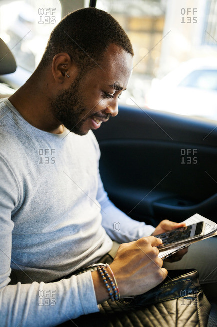 Young man using smartphone in taxi