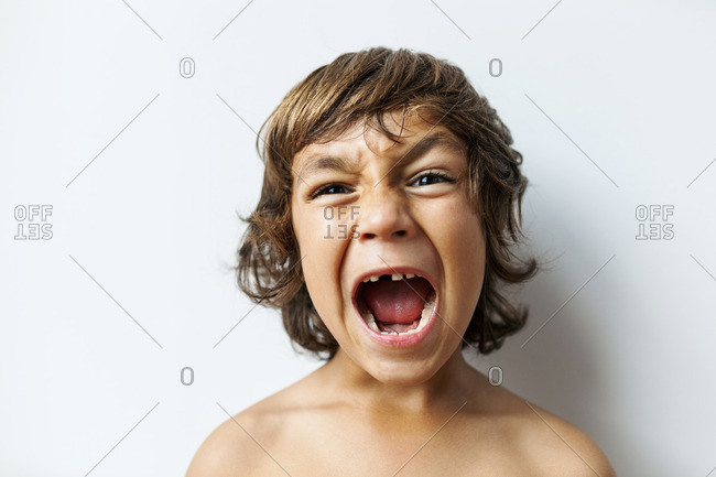 Portrait of screaming little boy with tooth gap in front of white background