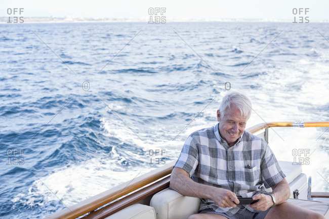 Senior man on a boat trip looking at cell phone