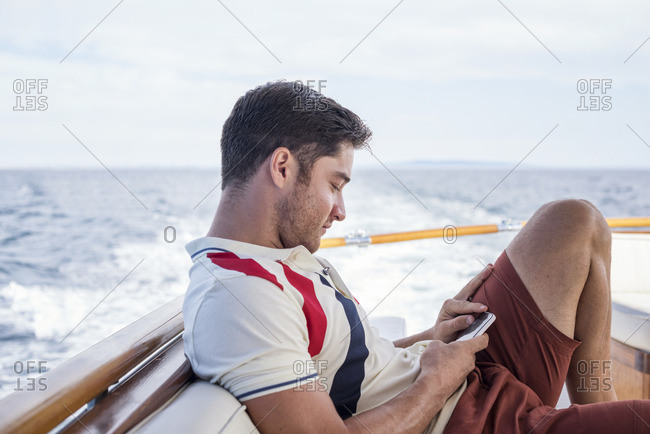 Young man on a boat trip looking at cell phone