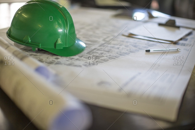 Construction helmet on blueprints in site office