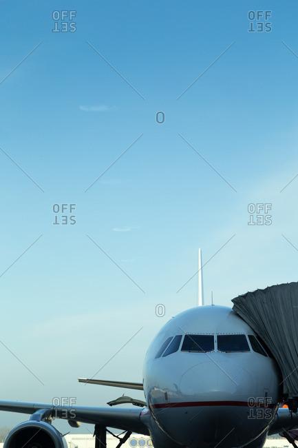 Airplane and passenger boarding bridge on a runway