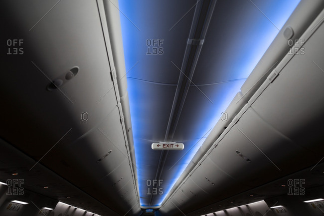 Aisle on an airplane with blue light illuminated
