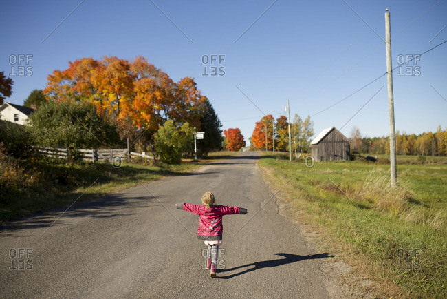 Little girl walking down a country road with her arms spread