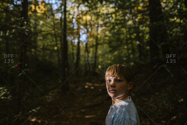Young boy walking through the woods looking back