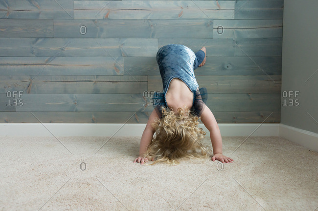 Little girl doing a handstand with her feet on a wall