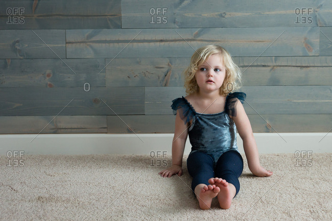 Little girl wearing leotard sitting on the floor looking away