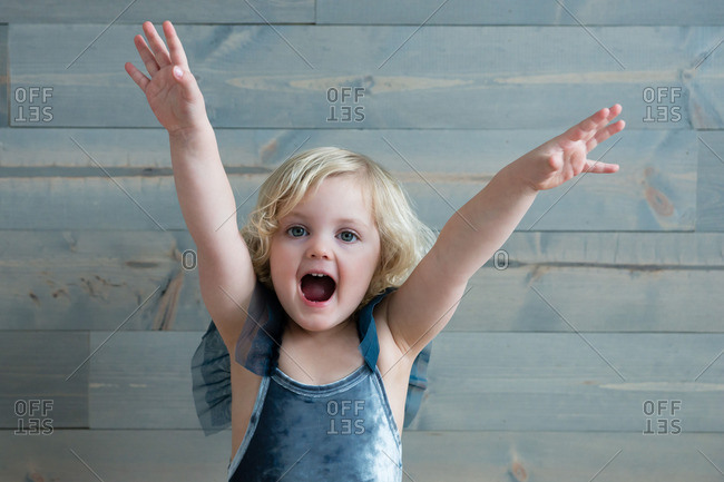 Little girl wearing leotard throwing her arms up in the air