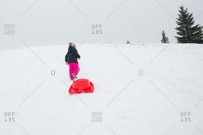 Little girl pulling a sled up a snowy hill