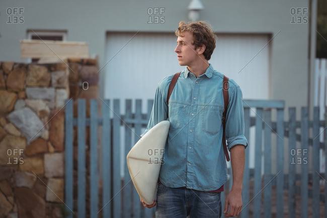 Man with backpack carrying a surfboard