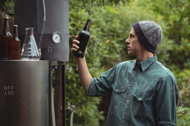 Man holding beer bottle while making beer at home brewery