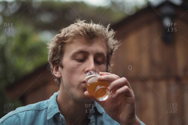 Close-up of man drinking beer from beer glass