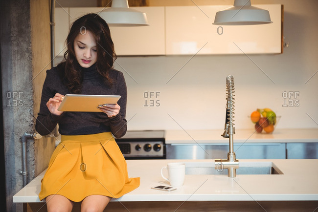 Woman sitting on kitchen worktop using digital tablet at home