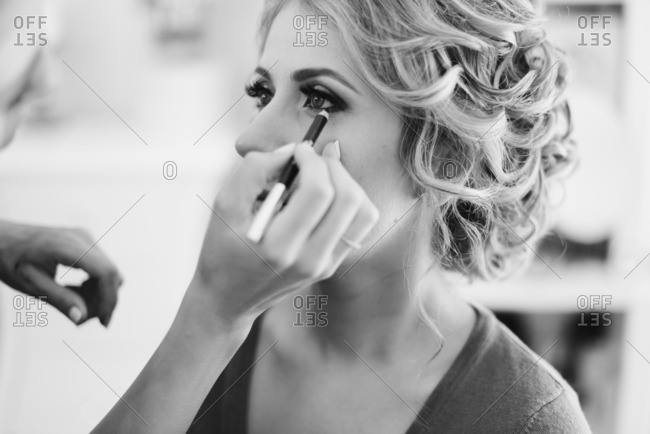 Person putting eyeliner on bride