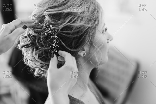 Putting accessory in bride's hair