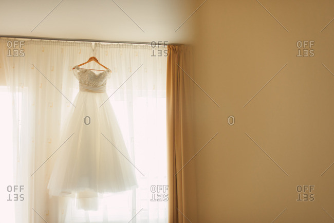 Bridal gown hanging in sunlit window