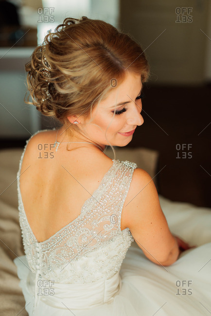 Bride looking down sitting on bed