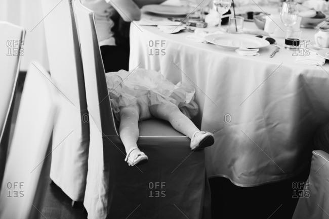 Girl lying in wedding reception chairs