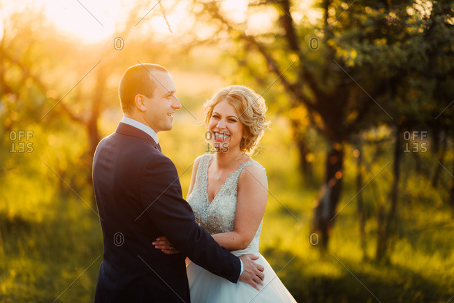 Grinning bride with groom in sunlight
