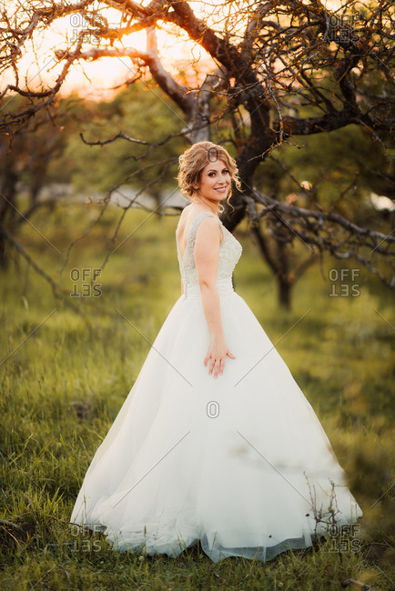 Bride in rural field at sunset