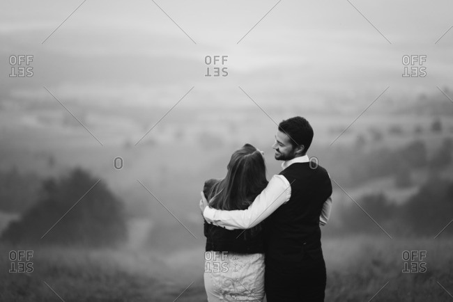 Bridal couple in embrace on misty hill