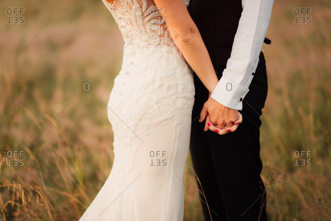 Clasped hands of bride and groom