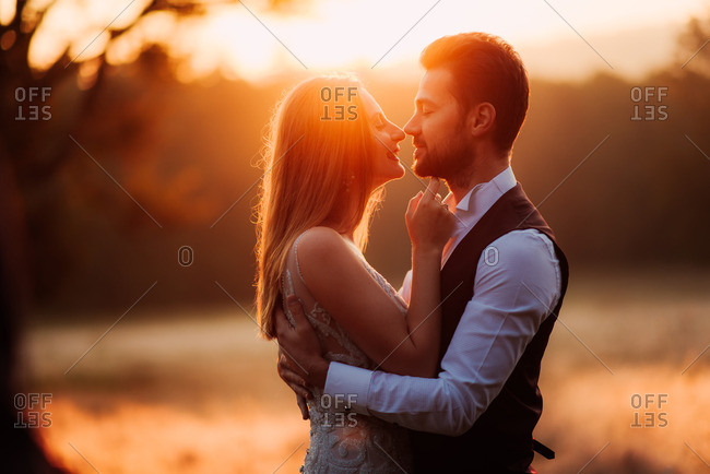Bridal couple in passionate embrace at sunset