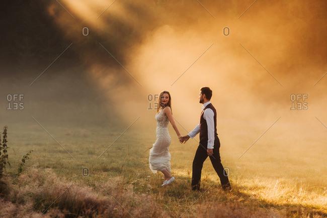 Bridal couple walking in sunbeams