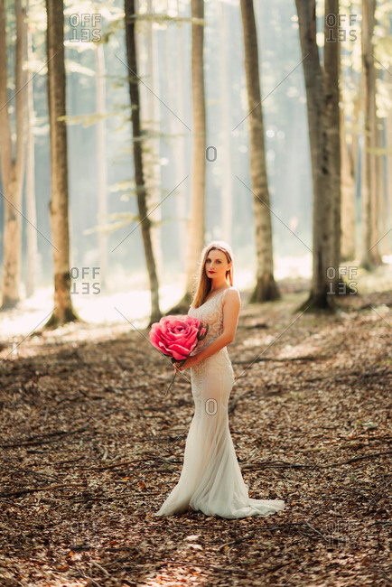 Bride in woods holding paper flower