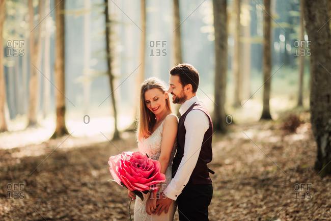 Groom hugging bride with paper flower