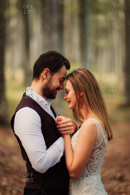 Bridal couple in tender forest embrace