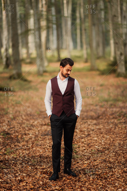 A groom standing alone in woods