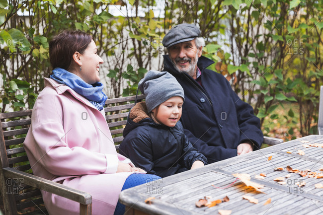 Happy senior man sitting with great grandson and daughter at wooden table in park