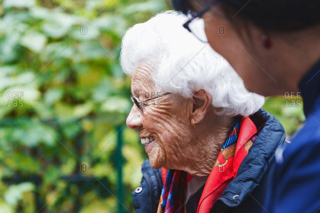 Side view of happy senior woman with caretaker in park