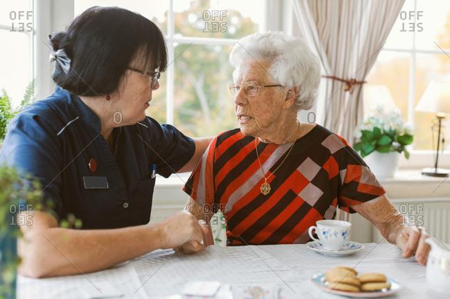 Female caretaker consoling senior woman at nursing home