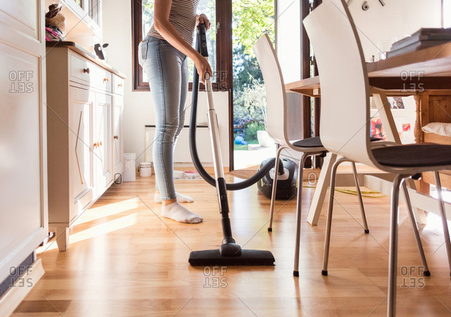 Low section of teenage girl cleaning hardwood floor with vacuum cleaner at home