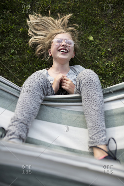 High angle view of smiling teenage girl lying on grass with feet up on hammock in backyard