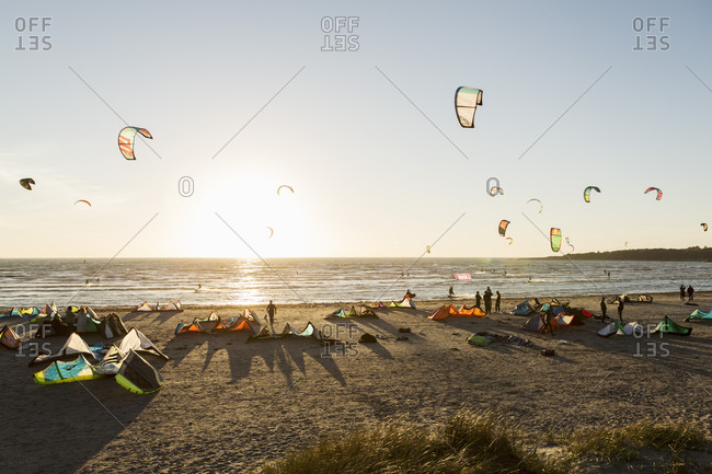 Kite boarders on beach against clear sky