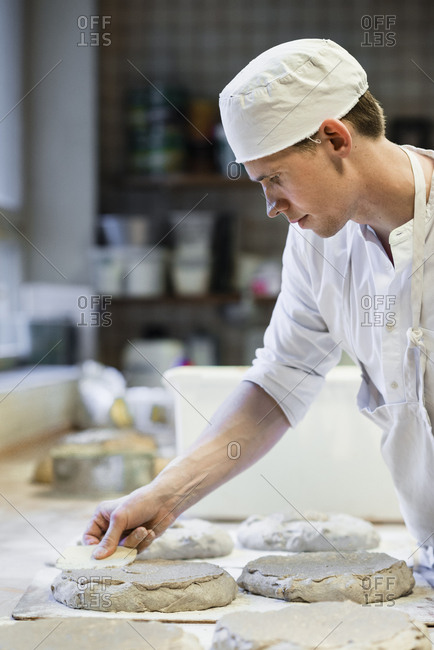Side view of chef making bread at commercial kitchen counter