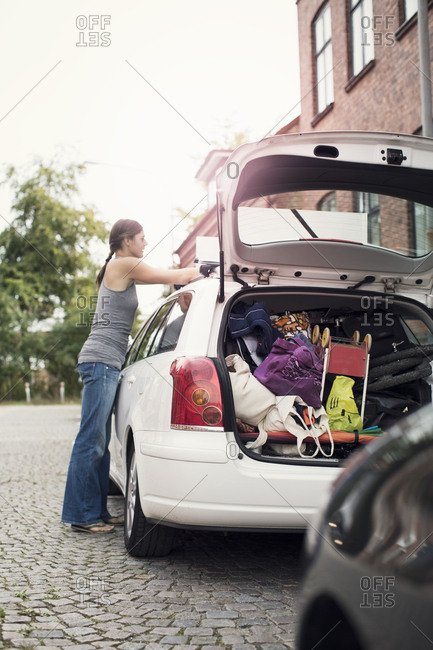 Side view of woman loading luggage on car roof