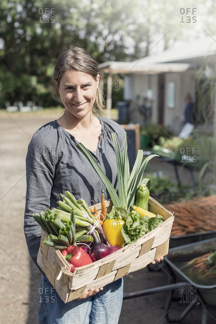 Portrait of happy woman carrying vegetables in basket