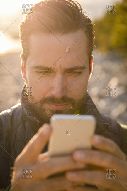 Close-up of man using mobile phone at beach