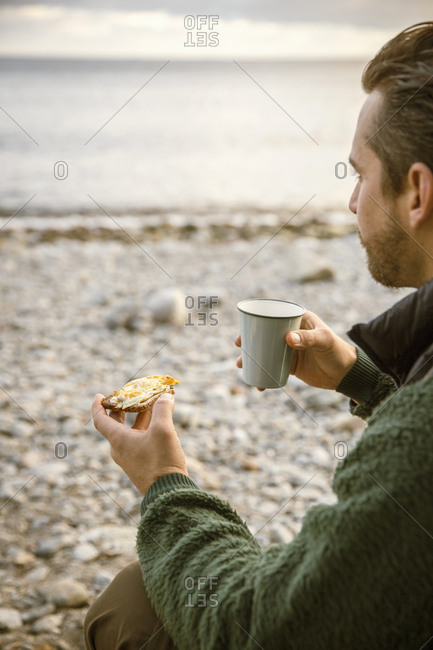 Cropped image of man eating snack with coffee at beach