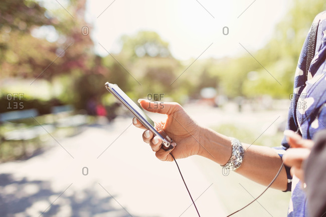 Cropped image of businesswoman holding smart phone on footpath at park