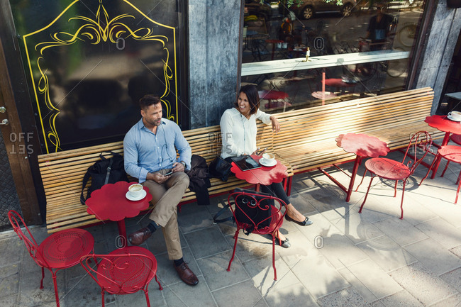 High angle view of business colleagues talking at sidewalk cafe